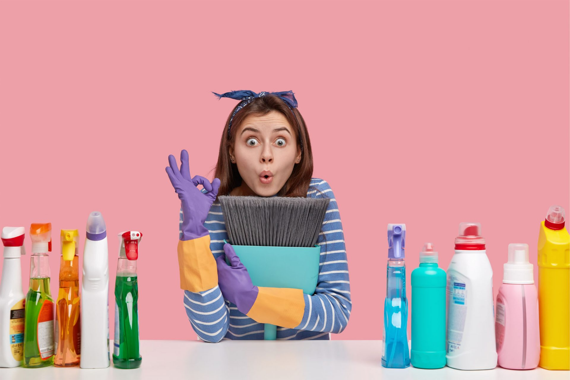 Indoor shot of surprised young Caucasian woman makes okay gesture, keeps broom closely, shows everything is ok, sweeps floor, cleans house with different detergents, dressed in striped jumper